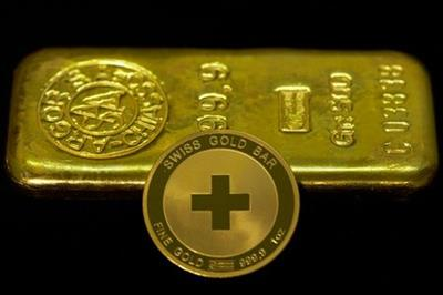 """An ounce of gold coin is pictured in front of a 500g ingot at Jolliet numismatic shop in Geneva November 19, 2014. Support among Swiss voters for a referendum proposal that would force a huge increase in the central bank's gold reserves has slipped to 38 percent percent, an opinion poll showed on Wednesday, falling short of the majority backing it needs to become law. Under the """"Save our Swiss gold"""" proposal, the Swiss National Bank (SNB) would be banned from selling any of its gold reserves and would have hold at least 20 percent of its assets in the metal, compared with 7.8 percent last month. REUTERS/Denis Balibouse (SWITZERLAND - Tags: POLITICS BUSINESS)"""