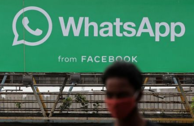 A man walks past a hoarding of the WhatsApp application installed at a skywalk in Mumbai, India, August 26, 2021. REUTERS/Francis Mascarenhas