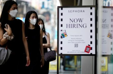 A sign advertising job openings is seen while people walk into the store in New York City, New York, U.S., August 6, 2021. REUTERS/Eduardo Munoz