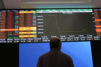 A man stands in front of an electronic display at B3 Brazilian Stock Exchange after an automatic circuit breaker was triggered this morning, in Sao Paulo, Brazil, March 16, 2020 REUTERS/Rahel Patrasso