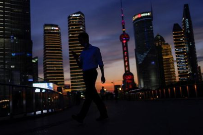 A man checks his phone while walking in Lujiazui financial district during sunset in Pudong, Shanghai, China July 13, 2021. Picture taken July 13, 2021. REUTERS/Aly Song