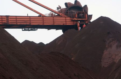 FILE PHOTO: Workers are seen on the top of an iron ore pile as a machine works on blending the iron ore, at Dalian Port, Liaoning province, China September 21, 2018. Picture taken September 21, 2018. REUTERS/Muyu Xu