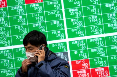 FILE PHOTO: A man wearing a protective face mask, following an outbreak of the coronavirus, talks on his mobile phone in front of a screen showing the Nikkei index outside a brokerage in Tokyo, Japan, February 26, 2020. REUTERS/Athit Perawongmetha/File Photo