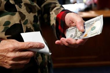 66-year-old Republican Eric Merrill of New Boston, New Hampshire, holds 1000 dollars in cash to file declaration of candidacy papers with New Hampshire Secretary of State Bill Gardner to appear on the 2020 New Hampshire presidential primary election ballot at the State House in Concord, New Hampshire, U.S., November 8, 2019. REUTERS/Mike Segar