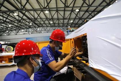 Employees work on assembling an automated guided vehicle (AGV) at a Lonyu Robot Co factory in Tianjin, China, September 7, 2021. Picture taken September 7, 2021. REUTERS/Tingshu Wang