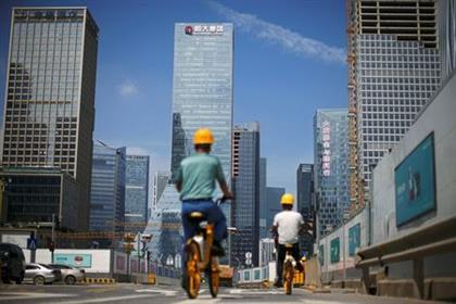 Men ride bicycles past construction sites near the headquarters of China Evergrande Group in Shenzhen, Guangdong province, China September 26, 2021. REUTERS/Aly Song