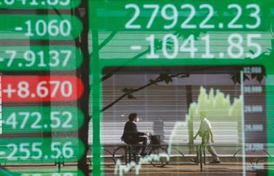 People are reflected on an electric board showing Nikkei index and its graph outside a brokerage at a business district in Tokyo, Japan, June 21, 2021. REUTERS/Kim Kyung-Hoon