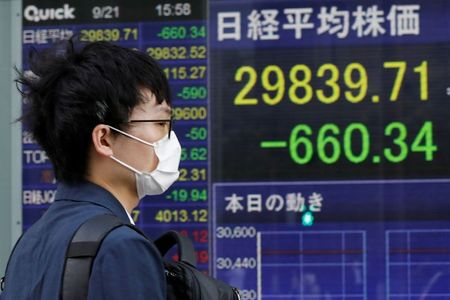 A man wearing a protective mask, amid the COVID-19 outbreak, walks past an electronic board displaying Japan's Nikkei index outside a brokerage in Tokyo, Japan, September 21, 2021. REUTERS/Kim Kyung-Hoon