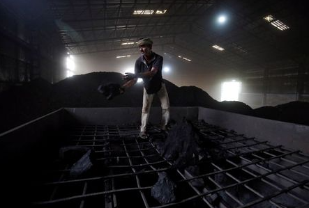 A labourer works inside a coal yard on the outskirts of Ahmedabad, India, April 6, 2017. REUTERS/Amit Dave