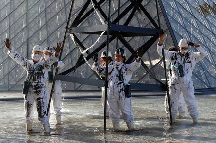 Greenpeace activists stand next to an oil drilling rig replica in front of the glass Pyramid of the Louvre museum during a protest in Paris as part of the launching of an European Citizens' Initiative (ECI) petition by 20 organisations calling for a new law that bans fossil fuel advertising and sponsorship in the European Union, France, October 6, 2021. REUTERS/Gonzalo Fuentes