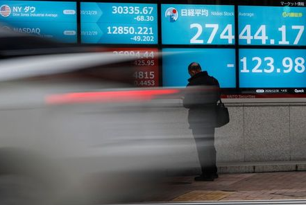 A man stands in front of a screen displaying Nikkei share average and the world's stock indexes outside a brokerage, amid the coronavirus disease (COVID-19) outbreak, in Tokyo, Japan December 30, 2020. REUTERS/Issei Kato