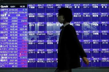 A passerby wearing a protective mask is silhouetted in front of a screen of blank prices on a stock quotation board after Tokyo Stock Exchange temporarily suspended all trading due to system problems, amid the coronavirus disease (COVID-19) pandemic, in Tokyo, Japan October 1, 2020. REUTERS/Issei Kato