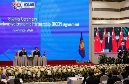 Vietnam's Prime Minister Nguyen Xuan Phuc (L) sits next to Minister of Industry and Trade Tran Tuan Anh as they watch a screen showing Chinese Minister of Commerce Zhong Shan (R) signing next to Chinese Premier Li Keqiang during the virtual signing ceremony of the Regional Comprehensive Economic Partnership (RCEP) Agreement during the 37th ASEAN Summit in Hanoi, Vietnam November 15, 2020. REUTERS/Kham/File photo