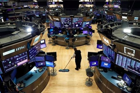A man cleans up on the trading floor, following traders testing positive for Coronavirus disease (COVID-19), at the New York Stock Exchange (NYSE) in New York, U.S., March 19, 2020. REUTERS/Lucas Jackson