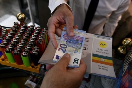 FILE PHOTO: A man uses cash to pay for items while shopping in Milan, Italy, October 2, 2020. Picture taken October 2, 2020. REUTERS/Flavio Lo Scalzo/File Photo