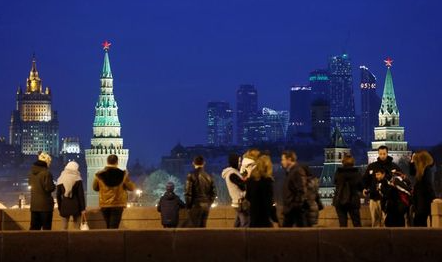 "People stand on the Great Moskvoretsky Bridge, with the headquarters of Russian Foreign Ministry, the Kremlin towers and the Moscow International Business Center also known as ""Moskva-City"", seen in the background, in central Moscow, Russia, March 28, 2016. REUTERS/Maxim Shemetov/File Photo"