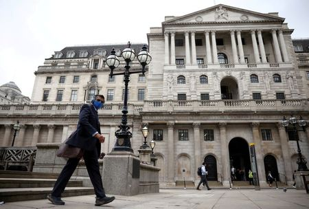 FILE PHOTO: A person walks past the Bank of England in the City of London financial district, in London, Britain, June 11, 2021. REUTERS/Henry Nicholls