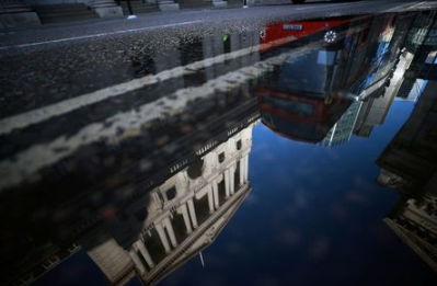 The Bank of England and the City of London financial district are reflected in a puddle, in London, Britain, December 17, 2020. REUTERS/Hannah McKay