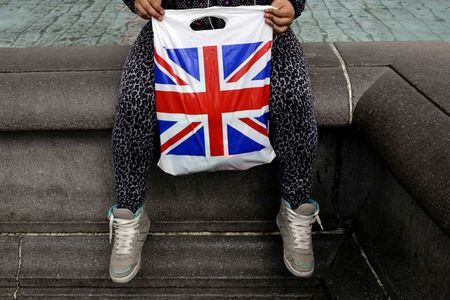 A woman holds a Union Flag shopping bag in London, Britain April 23, 2016. REUTERS/Kevin Coombs/File Photo GLOBAL BUSINESS WEEK AHEAD PACKAGE Ð SEARCH ÒBUSINESS WEEK AHEAD SEPTEMBER 12Ó FOR ALL IMAGES