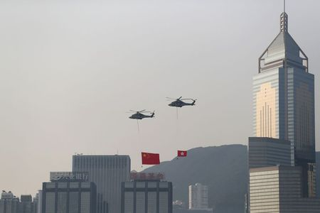 Helicopters carrying China's national flag and Hong Kong's flag fly past the skyline of Victoria Harbour on China's National Day in Hong Kong, China October 1, 2019. REUTERS/Athit Perawongmetha