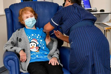 Margaret Keenan, 90, is the first patient in Britain to receive the Pfizer/BioNtech COVID-19 vaccine at University Hospital, administered by nurse May Parsons, at the start of the largest ever immunisation programme in the British history, in Coventry, Britain December 8, 2020. Britain is the first country in the world to start vaccinating people with the Pfizer/BioNTech vaccine. Jacob King/Pool via REUTERS TPX IMAGES OF THE DAY