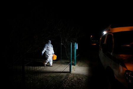A paramedic wearing personal protective equipment (PPE) walks towards an ambulance as she leaves the house of a patient, amid the outbreak of the coronavirus disease (COVID-19) in the town of Soltsy, Novgorod Region, Russia December 10, 2020. Picture taken December 10, 2020. REUTERS/Anton Vaganov