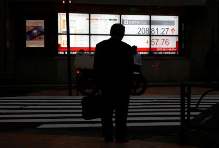 A man stands in front of an electronic board showing Japan's Nikkei average outside a brokerage in Tokyo, Japan October 11, 2017. REUTERS/Toru Hanai