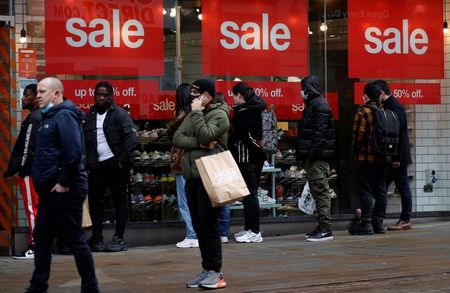 Shoppers queue to enter a shoe shop at the start of the Boxing Day sales amid the outbreak of the coronavirus disease (COVID-19) in Manchester, Britain, December 26, 2020. REUTERS/Phil Noble
