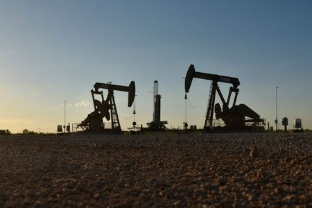 FILE PHOTO: Pump jacks operate in front of a drilling rig in an oil field in Midland, Texas U.S. August 22, 2018. Picture taken August 22, 2018. REUTERS/Nick Oxford/File Photo