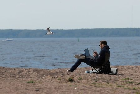 A man uses his smartphone and laptop as he sits on the shore of the Gulf of Finland amid the outbreak of the coronavirus disease (COVID-19) in Saint Petersburg, Russia May 27, 2020. REUTERS/Anton Vaganov