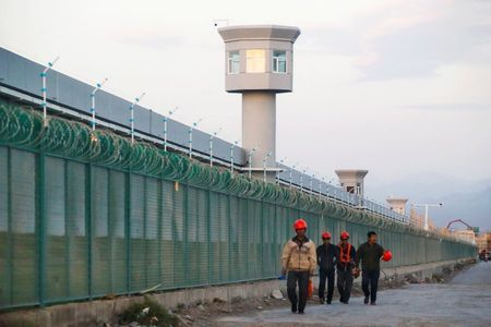 FILE PHOTO: Workers walk by the perimeter fence of what is officially known as a vocational skills education centre in Dabancheng in Xinjiang Uighur Autonomous Region, China September 4, 2018. Picture taken September 4, 2018. REUTERS/Thomas Peter/File Photo