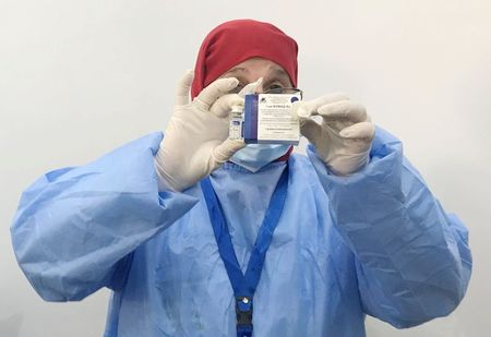 A healthcare worker holds a box and a vial of the Sputnik V vaccine against the coronavirus disease (COVID-19), during a national vaccination campaign, in Algiers, Algeria January 31, 2021. REUTERS/Abdelaziz Boumzar