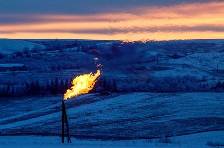 FILE PHOTO: A natural gas flare on an oil well pad burns as the sun sets outside Watford City, North Dakota January 21, 2016. REUTERS/Andrew Cullen/File Photo