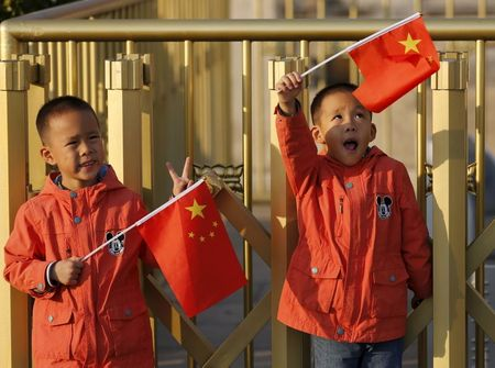 Twin boys Sun Qiyu and Sun Qichun hold China's national flags on the Tiananmen Gate in Beijing November 2, 2015. China must continue to enforce its one-child policy until new rules allowing all couples to have two children go into effect, the top family planning body said. The ruling Communist Party said last week that Beijing would loosen its decades-old one-child policy. The plan for the change must be approved by the rubber-stamp parliament during its annual session in March. REUTERS/Kim Kyung-Hoon