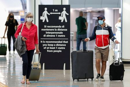 """Passengers wearing protective face masks walk at Fiumicino Airport on the day EU governments agreed a """"safe list"""" of 14 countries for which they will allow non-essential travel starting from July, following the coronavirus disease (COVID-19) outbreak, in Rome, Italy, June 30, 2020. REUTERS/Guglielmo Mangiapane"""