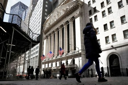 FILE PHOTO: People are seen on Wall Street outside the New York Stock Exchange (NYSE) in New York City, U.S., March 19, 2021. REUTERS/Brendan McDermid