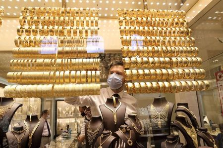 FILE PHOTO: A goldsmith wearing a protective face mask arranges golden bangles as the other talks to customers at a jewellery shop at the Grand Bazaar in Istanbul, Turkey, August 6, 2020. Picture taken August 6, 2020. REUTERS/Murad Sezer/File Photo