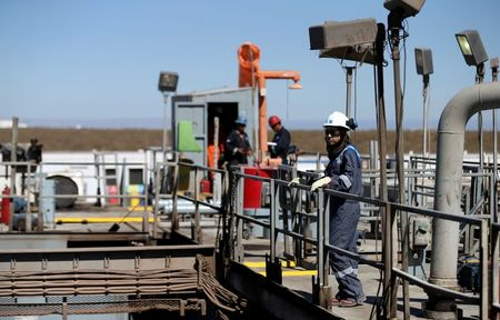 FILE PHOTO: A worker looks on over a platform in a drilling rig at Vaca Muerta shale oil and gas drilling, in the Patagonian province of Neuquen, Argentina January 21, 2019. Picture taken January 21, 2019. REUTERS/Agustin Marcarian/File Photo
