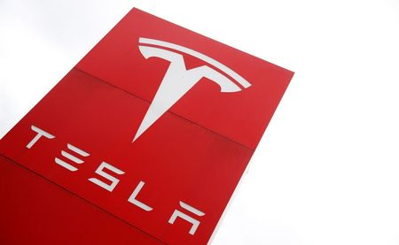 The logo of car manufacturer Tesla is seen at a dealership in London, Britain, May 14, 2021. REUTERS/Matthew Childs