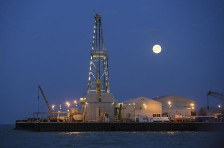 The full moon rises in the background over an oil rig at the Kashagan offshore oil field in the Caspian sea in western Kazakhstan August 21, 2013. After costing nearly $50 billion, mostly paid by some of the world's top oil companies, Kashagan may now be delayed until 2015, jeopardising a forecast budget boost for Kazakhstan of $28 billion - about a third - between 2014 and 2016. Picture taken August 21, 2013. To match Insight KAZAKHSTAN-KASHAGAN/INSIGHT REUTERS/Stringer (KAZAKHSTAN - Tags: ENERGY BUSINESS ENVIRONMENT)