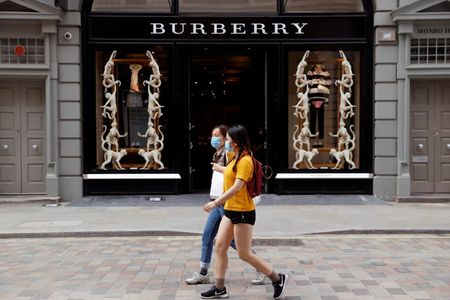 People wearing protective masks walk past a Burberry store at Covent Garden, following the outbreak of the coronavirus disease (COVID-19) in London, Britain June 15, 2020. REUTERS/John Sibley