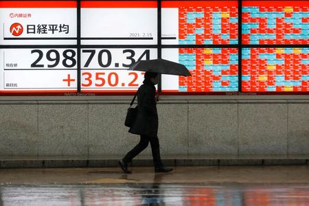 A man holding an umbrella walks in front of an electric board showing Nikkei index a brokerage in Tokyo, Japan February 15, 2021. REUTERS/Kim Kyung-Hoon