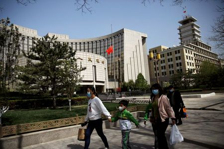 People wearing face masks walk past the headquarters of Chinese central bank People's Bank of China (PBOC), where the Chinese national flag flies at half mast in Beijing as China holds a national mourning for those who died of the coronavirus disease (COVID-19), on the Qingming tomb-sweeping festival, April 4, 2020. REUTERS/Tingshu Wang