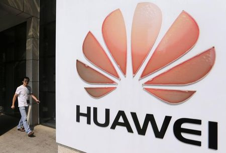 A man walks past a Huawei company logo outside the entrance of a Huawei office in Wuhan, Hubei province October 9, 2012. The U.S. ambitions of two Chinese telecom equipment makers were stopped in their tracks on Monday as a congressional report urged American companies to stop doing business with the firms, raising fears of retaliation from China. Huawei, the world's second-largest maker of routers and other telecom gear, and ZTE, the fifth-largest, for years have been stymied in their efforts to make big inroads into the United States due to national security concerns, but Monday's report escalated the dispute. REUTERS/Stringer (CHINA - Tags: POLITICS BUSINESS TELECOMS LOGO SCIENCE TECHNOLOGY) CHINA OUT. NO COMMERCIAL OR EDITORIAL SALES IN CHINA