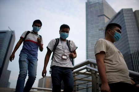 Men wearing protective masks walk on a bridge, following new cases of the coronavirus disease (COVID-19), in Shanghai, China August 23, 2021. REUTERS/Aly Song