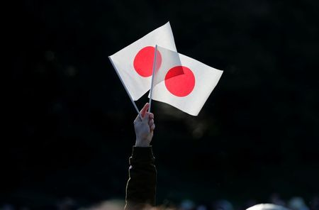 A well-wisher holds Japan's national flags during Emperor Naruhito's public appearance for New Year celebrations at the Imperial Palace in Tokyo, Japan, January 2, 2020. REUTERS/Kim Kyung-Hoon