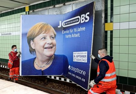 """Workers remove an advertisement showing German Chancellor Angela Merkel with a slogan that reads """"Mother of Nation - Thanks For 16 Years of Hard Work"""" before the upcoming state elections in Hamburg, Germany September 24, 2021. REUTERS/Fabian Bimmer TPX IMAGES OF THE DAY"""
